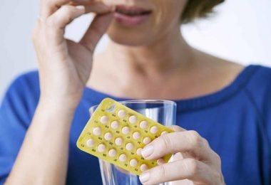Mujer tomando cápsulas reemplazo hormonal