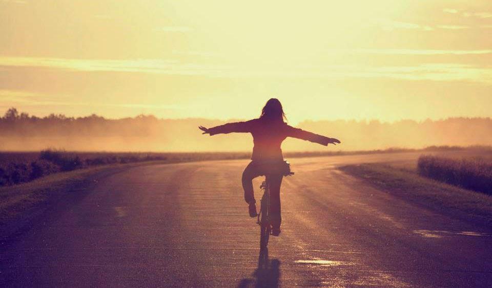 Mujer que maneja bicicleta y se siente libre de tener lo suficiente