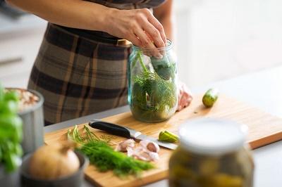 Pepinos en vinagre mujer cocinando cortando verduras