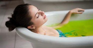 Mujer se baña en una tina con agua caliente y aceite de menta para aliviar los dolores musculares