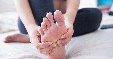 mujer realizando un automasaje en los pies