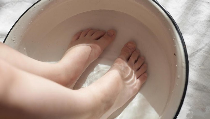 pies sumergidos en agua para tratar los hongos en las uñas