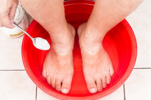 Mujer lavándose los pies usando bicarbonato de sodio un remedio efectivo para eliminarlos