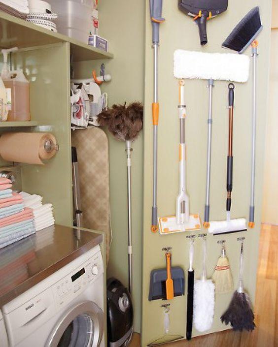 ahorrar espacio en la lavandería usando la puerta del almacén para colgar escobas