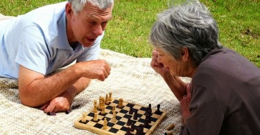 stock-footage-senior-couple-relaxing-in-the-park-lying-on-a-blanket-playing-chess-on-a-sunny-day