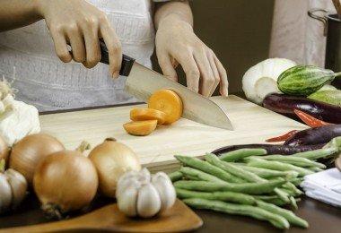Mujer partiendo vegetales cocinando