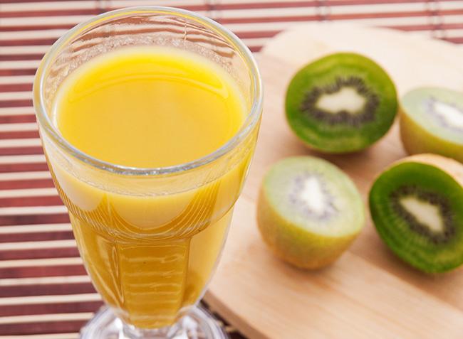 Un vaso con jugo de naranja y kiwi para aliviar los síntomas de la cistitis