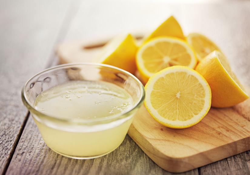Limones cortados y un vaso con jugo de limón