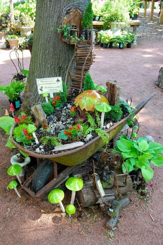jardn hecho sobre una carretilla que fue aprovechada para formar una linda maceta con pequeas plantas y sobre la cual sube una escalera a un pequeo