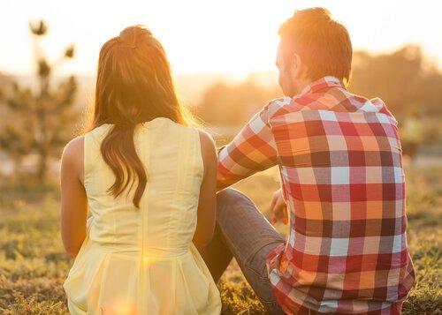 una pareja sentados juntos contemplando el atardecer