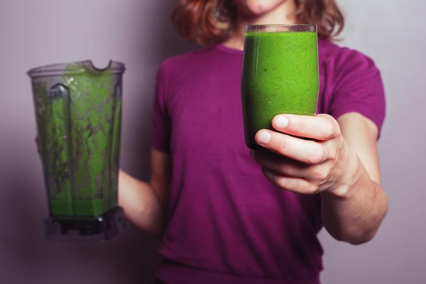 Mujer tomando jugo verde