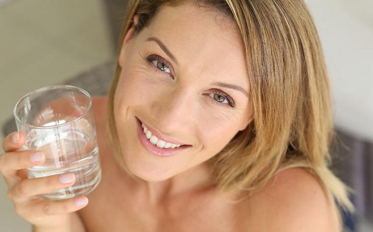 Mujer bebiendo agua para mantenerse hidratada y evitar estrias en los senos