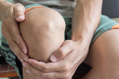 Hombre joven con dolor en la rodilla frotándose