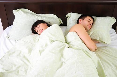 Pareja durmiendo de espaldas