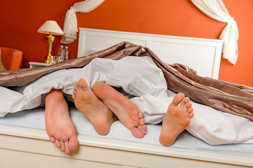 Pareja tocándose los pies en la cama