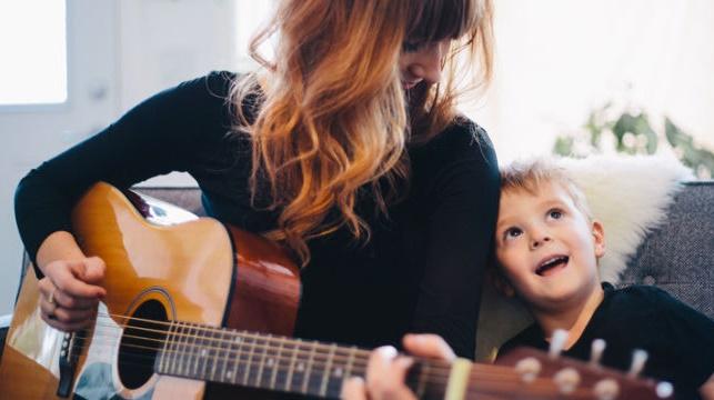 mamá emocionalmente fuerte tocando guitarra