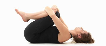 """Realizando la postura de yoga llamada """"Pavanamuktasana"""""""