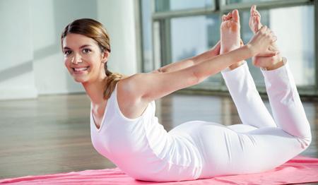 """Realizando la postura de yoga conocida como """"arco"""""""