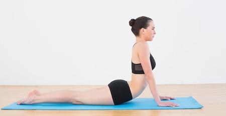 Mujer realizando la pose de la cobra, una postura de yoga clásica