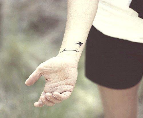 Tatuaje de un ave que emprede su vuelo