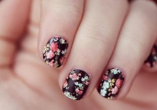 Uñas decoradas con flores sobre un fondo negro
