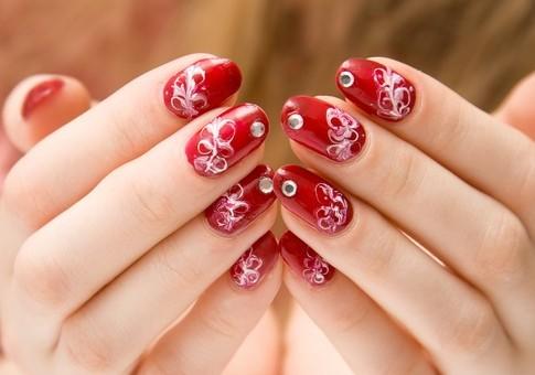 Uñas con tonos rojizos y colores de flores blancas