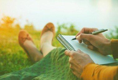 mujer escribiendo libreta campo