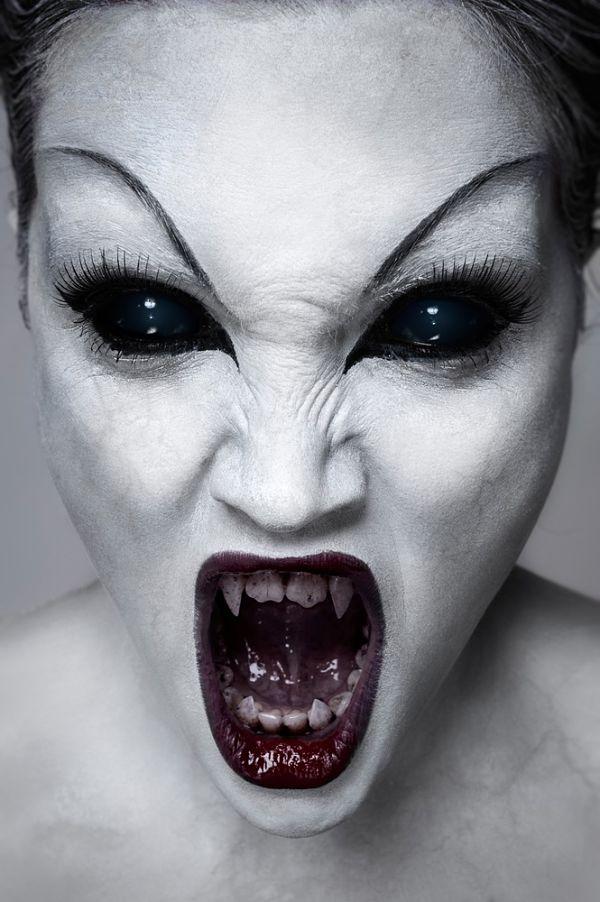 chica con maquillaje para halloween con colmillos y cara pintada de blanco