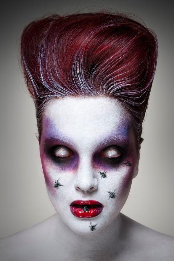 maquillaje para halloween que tiene forma de muerto viviente con ojos blanco y arañas en la cara