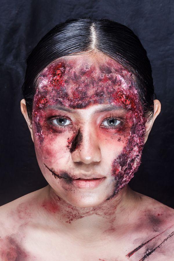 mujer con maquillaje para Halloween con el rostro pintado con heridas de color rojo