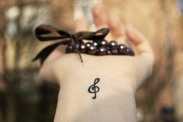 una chica con un tatuaje pequeño en su mano con el símbolo de la clave de sol
