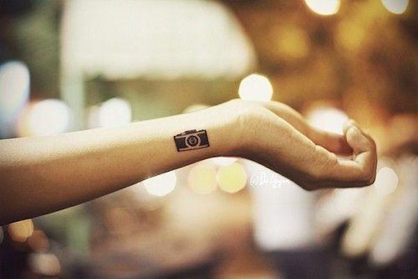 Mujer con un tatuaje en su mano con la imagen de una cámara de fotos