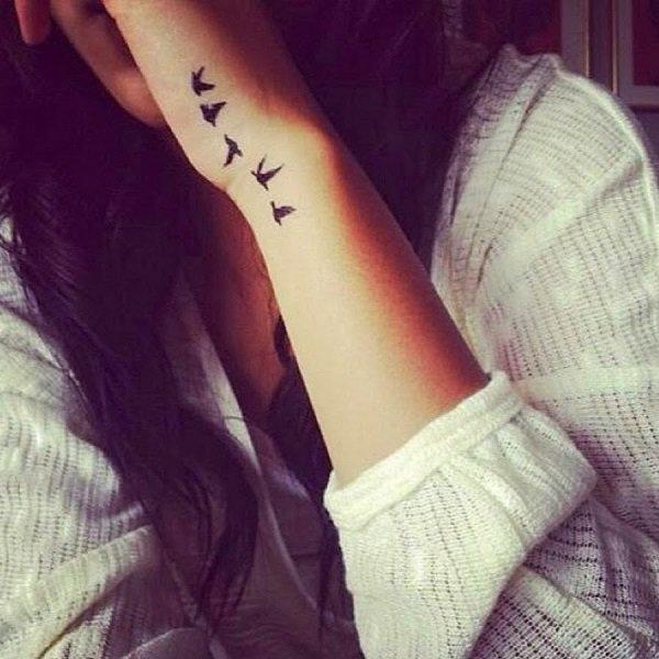 Chica con tatuaje de aves pequeñas volando con un significado de libertad