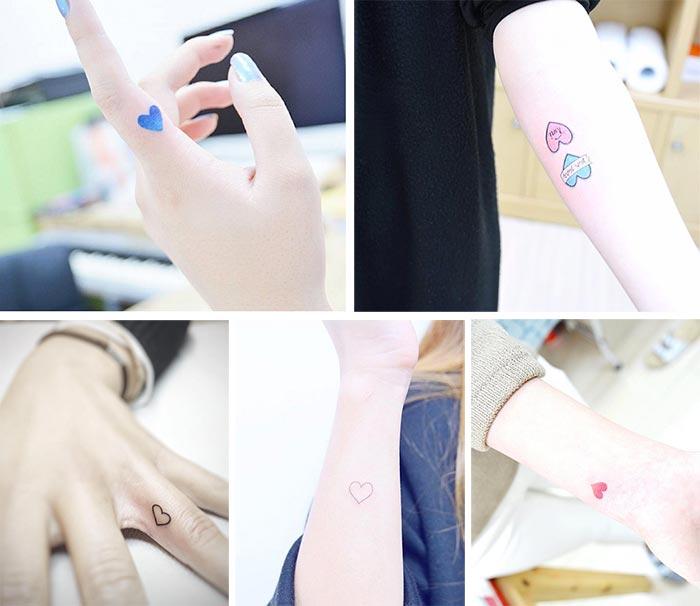 tatuajes pequeños de corazones de diferentes colores en manos y antebrazos.