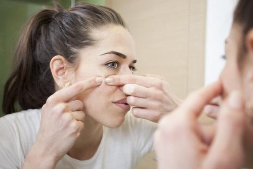 Mujer tratando de quitarse el acné es mejor consultar con un dermatólogo