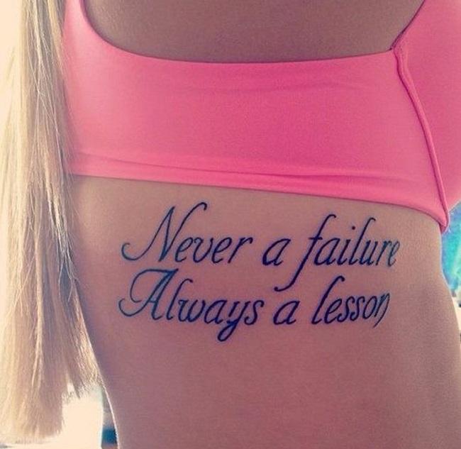 Una frase tatuada en el costdo del cuerpo en una joven mujer rubia