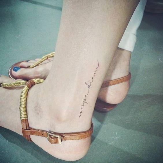 """Joven mujer blanca con una frase para tatuaje en su pierna que dice: """"Carpe Diem"""""""