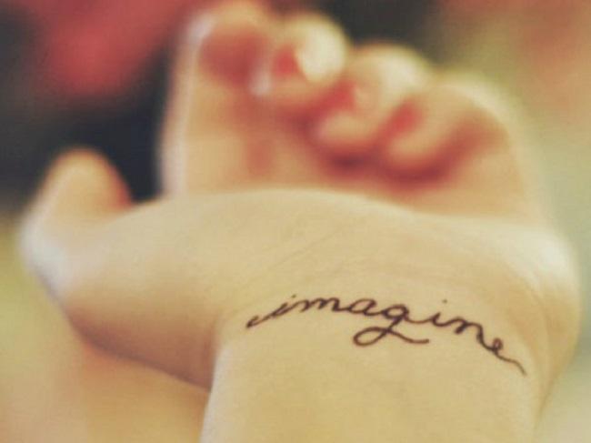 """Llevando un tatuaje en su mano con la frase """"imagina"""""""