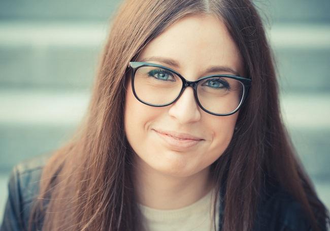 Una mujer con cara redonda que usa gafas redonda acentuando aún más sus rasgos
