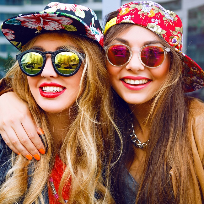 Chicas jóvenes luciendo unas monturas de gafas con vidrios de colores y redondeadas, al mejor estilo retro