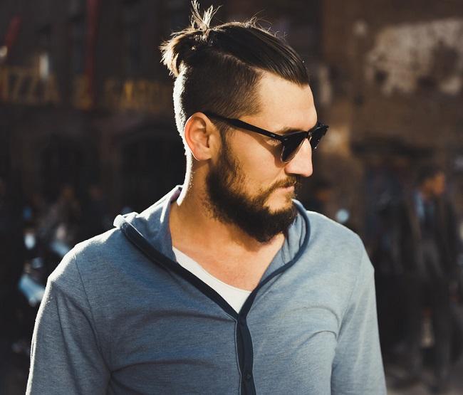 Hombre con pelo largo en la parte superior peinado hacia atrás y sujetado
