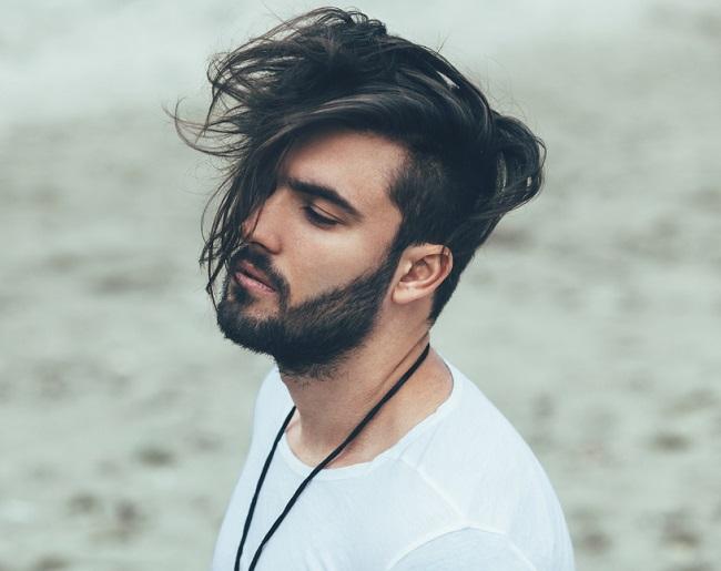 Mechones sobre el rostro con laterales cortos y barba, un estilode peinados para hombres este