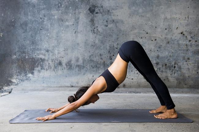 """Una joven mujer practicando la posición de yoga conocida como """"el perro"""""""