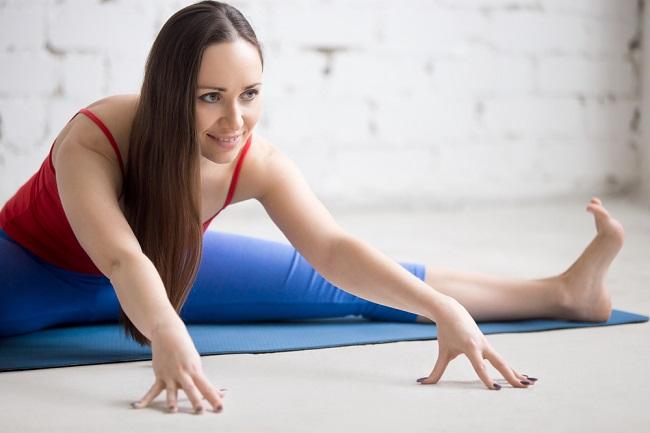 Una joven muchacha haciendo un estiramiento del yoga llamado Upavishtha Konasana