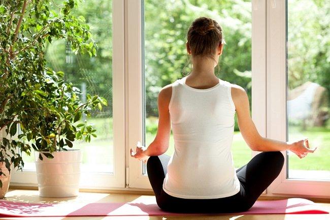 Mujer practicando yoga en casa durante la mañana