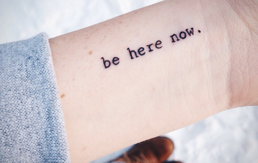 """pequeño tatuaje en el antebrazo que dice: """"estar aquí y ahora"""""""