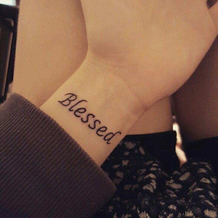 palabra bendecido tatuada en la muñeca de una mujer joven