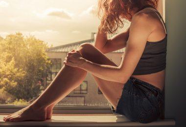 mujer viendo la ventana, nostalgia melancolía atardecer