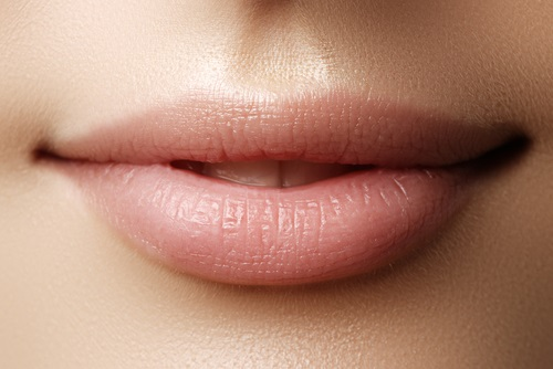 Labios de mujer que lucen naturales con maquillaje nude