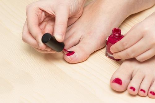 pintándose las uñas de los pies en pedicura casera